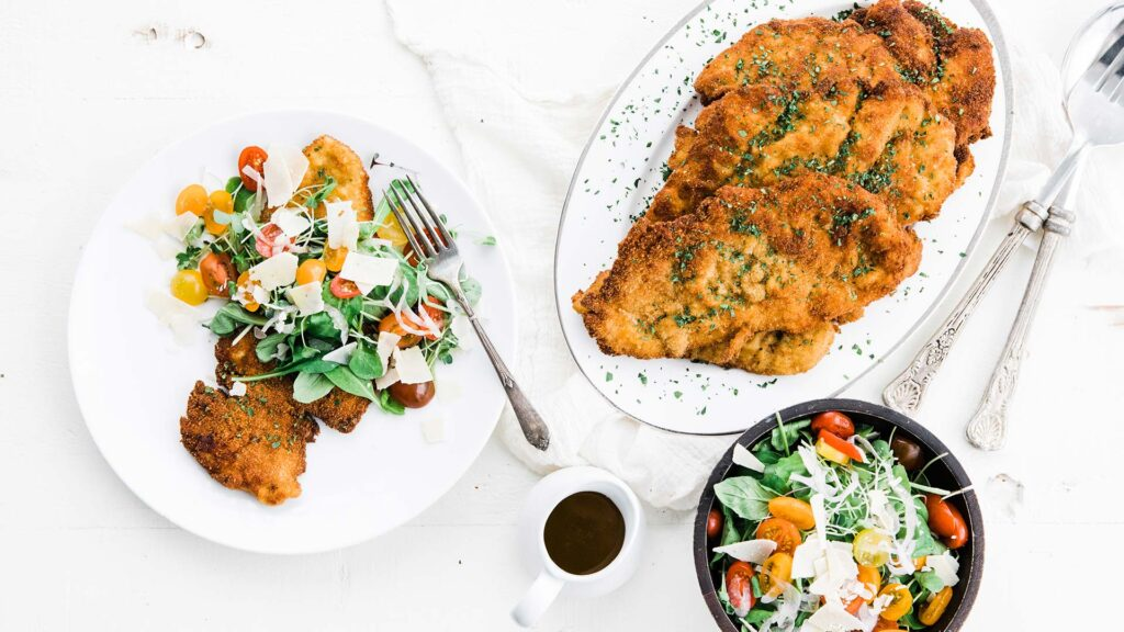 chicken milanese with arugula salad and fried chicken cutlets on a platter