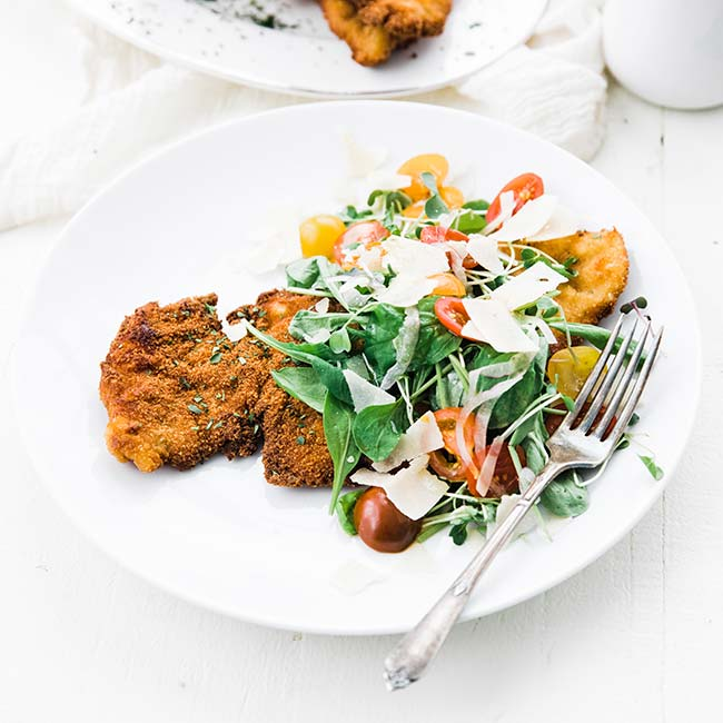 chicken milanese recipe with an arugula salad and parmesan cheese on a plate