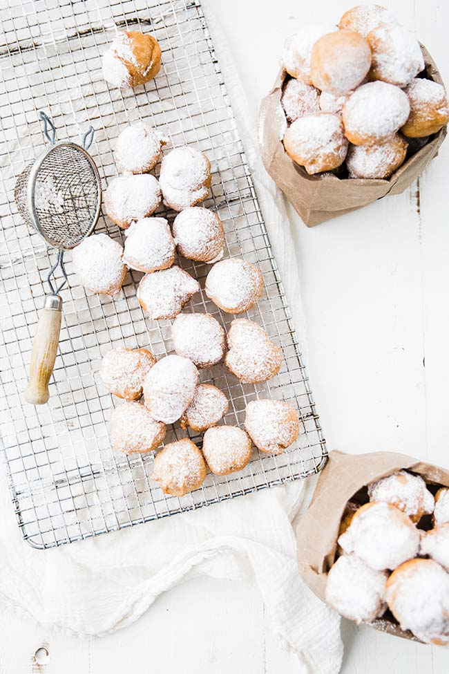 zeppoles with powdered sugar on a cooling rack