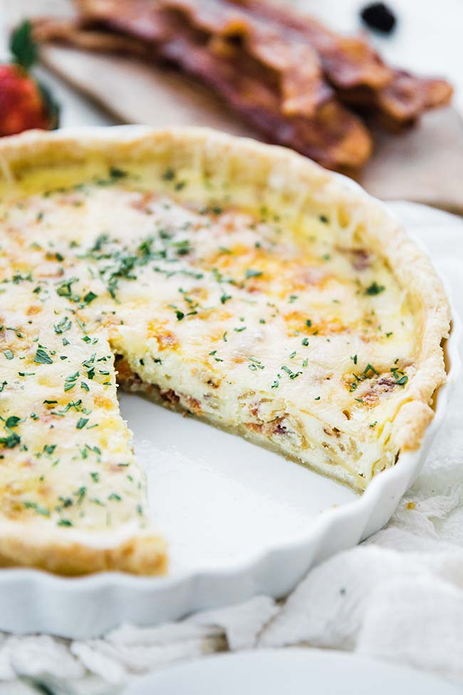 quiche lorraine recipe in a tart pan with a slice taken out
