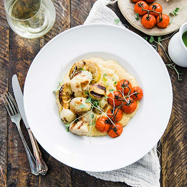 scallops with polenta and tomatoes on a plate