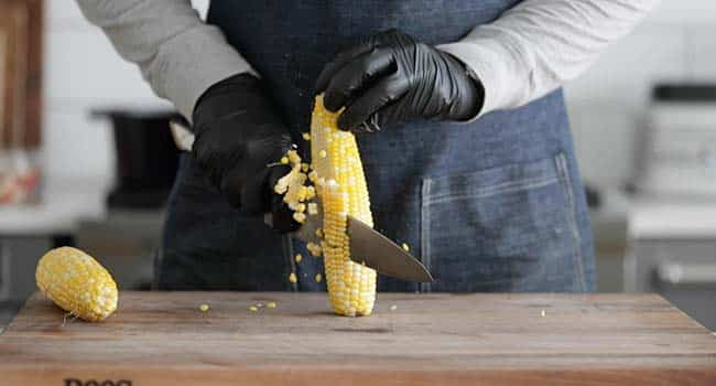 slicing cooked corn off of the cob