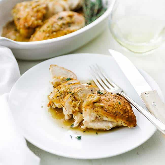 sliced cooked chicken breast on a plate with sauce