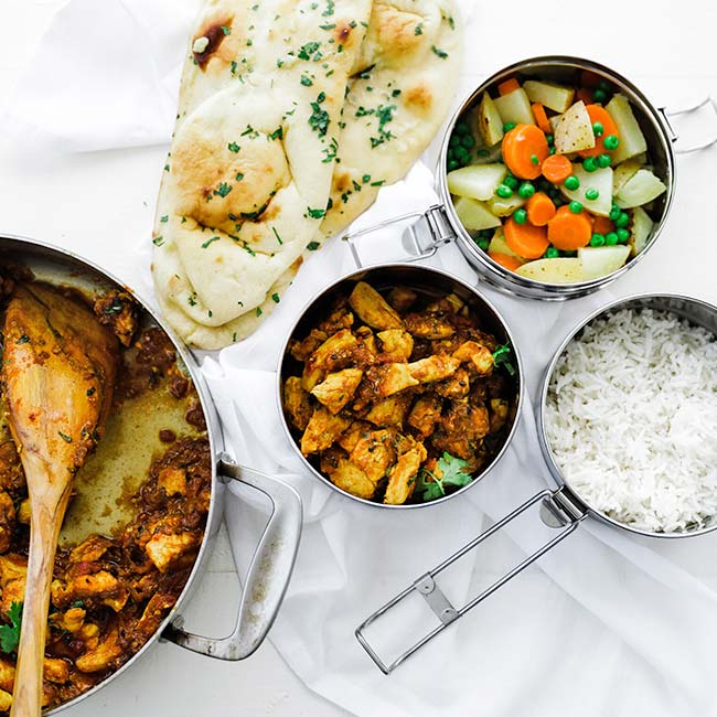 curry chicken in tiffin boxed with rice, naan and vegetables