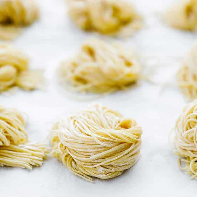 homemade pasta curled up in a ball on parchment paper
