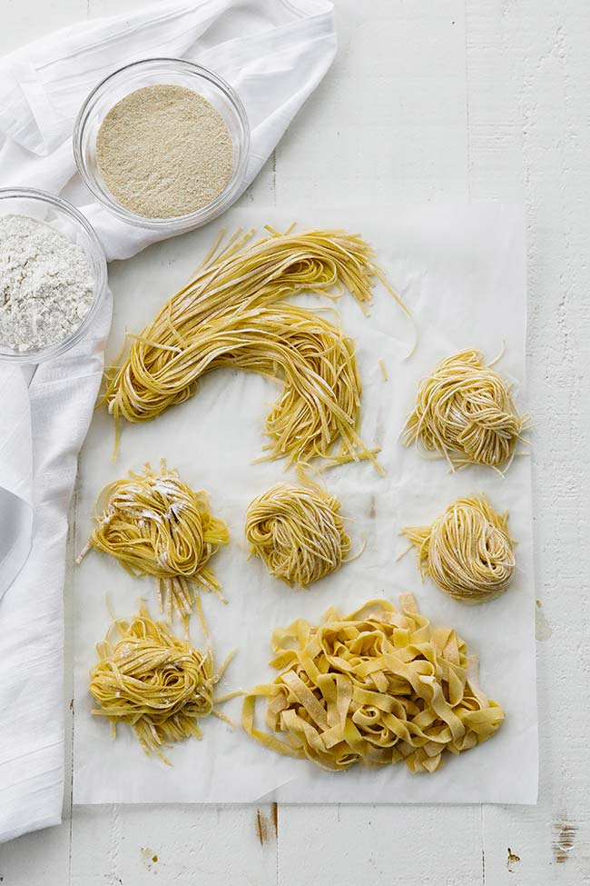 different pastas curled up on parchment paper