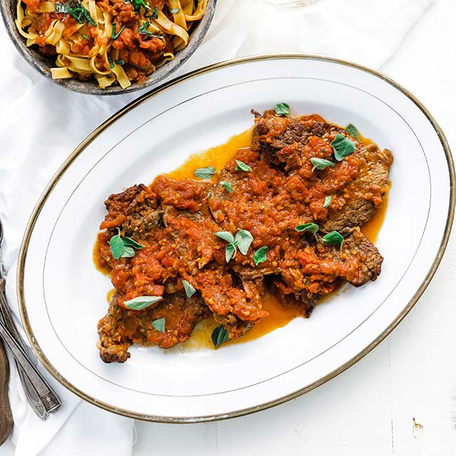 cooked steak with tomatoes sauce and oregano on a platter