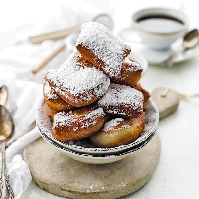 beignet donuts covered in powdered sugar and served with coffee