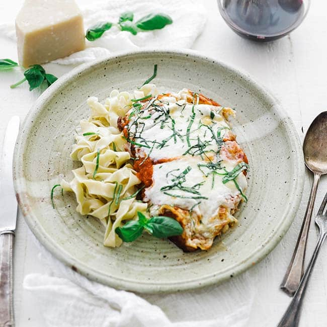 chicken parmesan with basil on a plate with buttered noodles