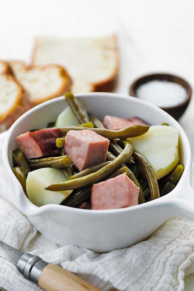 bowl of chunks of ham, green beans and potatoes with bread