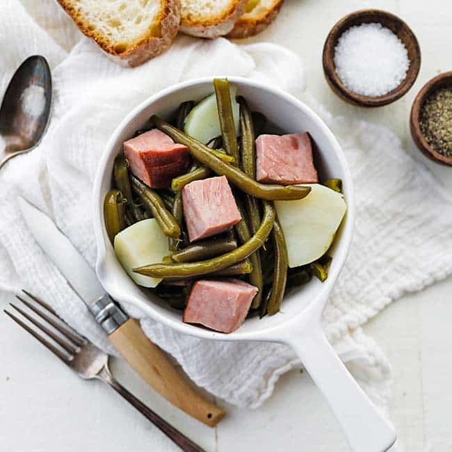 bowl with ham, green beans and potatoes next to sliced bread