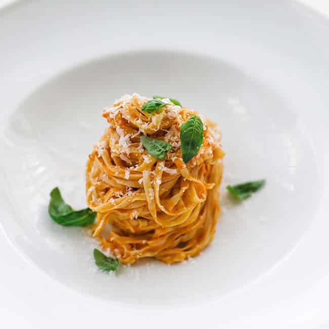 homemade pasta coated in pomodoro sauce with basil