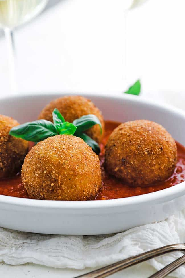 browned risotto arancini in a dish with tomato sauce and basil