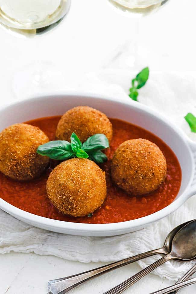 fried arancini balls with fresh basil and pomodoro sauce