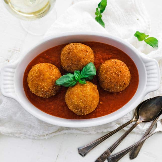 casserole dish with fried arancini balls and tomato sauce