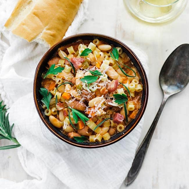 bowl of pasta and beans with fresh herbs