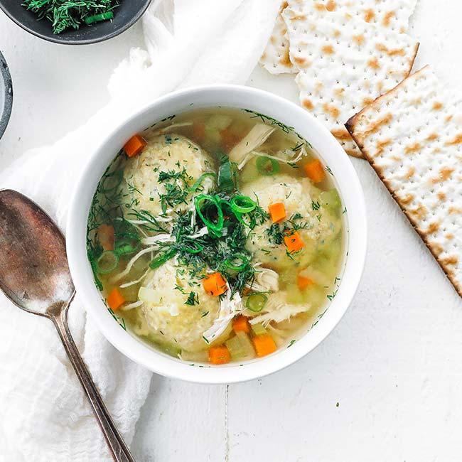 bowl of chicken stoup with matzo balls and fresh herbs