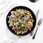 bowl of egg noodles with beef stroganoff and sauce