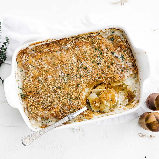 casserole dish full of potatoes au gratin with a spoon