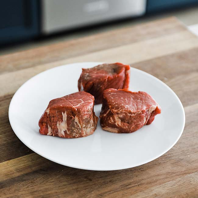 3 individual filet mignon steaks on a plate on a cutting board