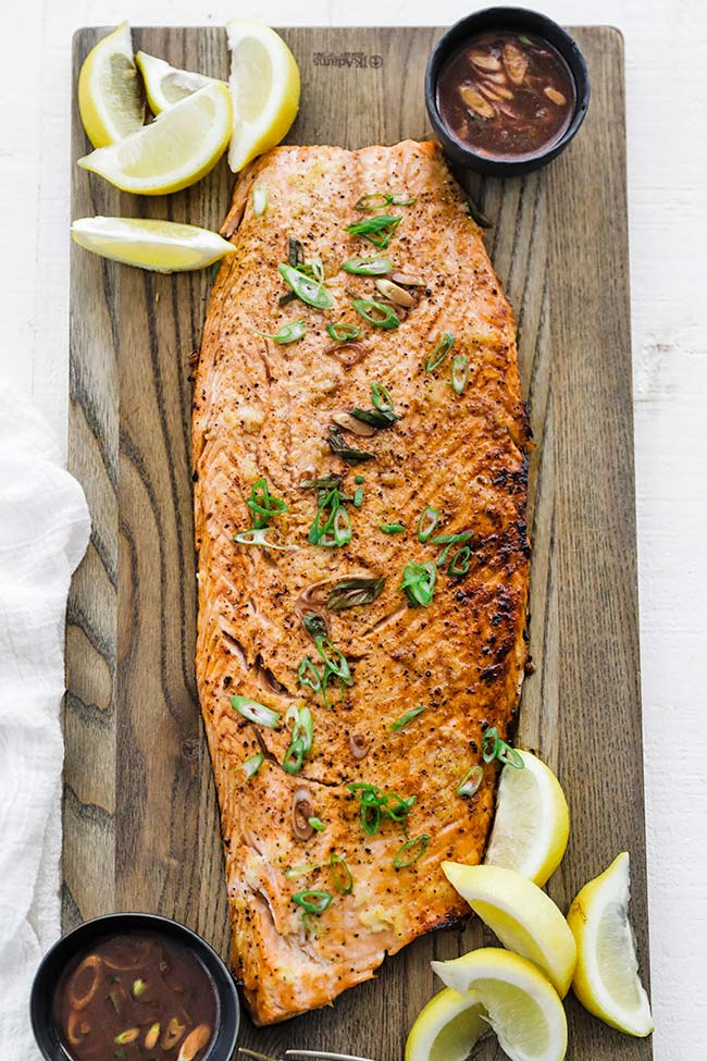 a whole side of cooked salmon with sauce and lemons on a cutting board