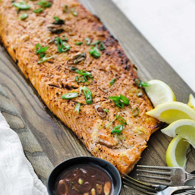 cooked salmon on a cutting board with herbs and lemons