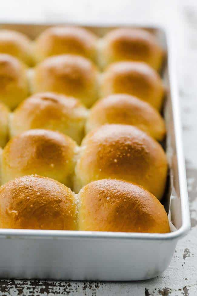 a large cooking pan full of browned rolls with salt and butter