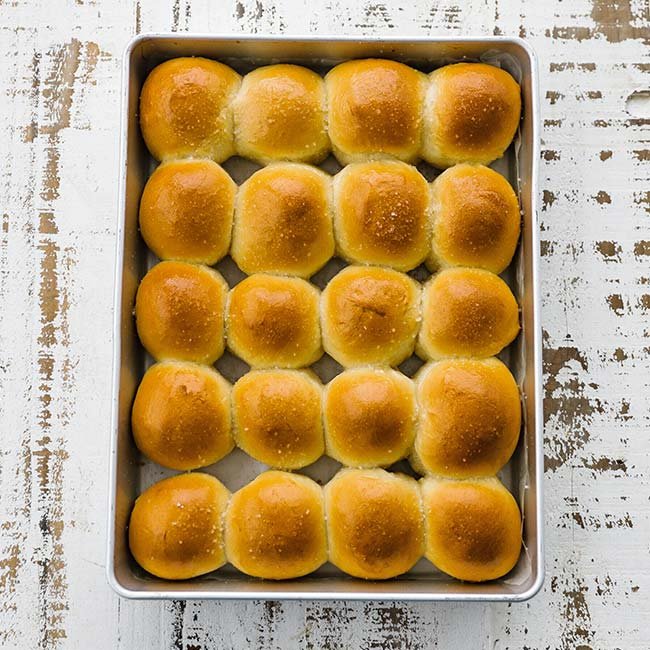 pan full of cooked and buttered dinner rolls