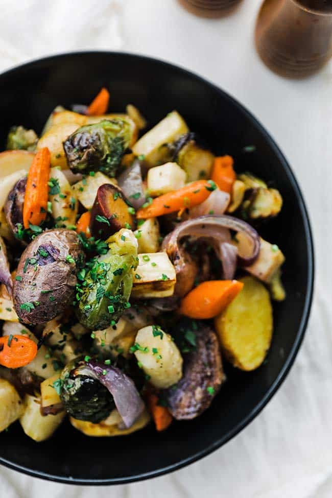 black bowl with roasted carrots, brussel sprouts, potatoes and onions
