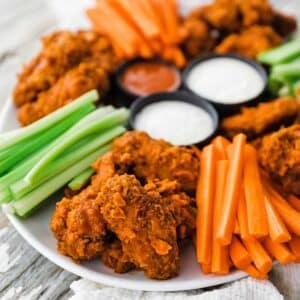 platter of buffalo wings with carrots and celery