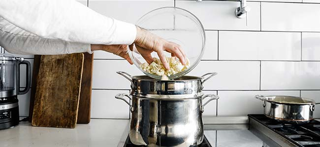 boiling a bowl of cauliflower in a pot of water