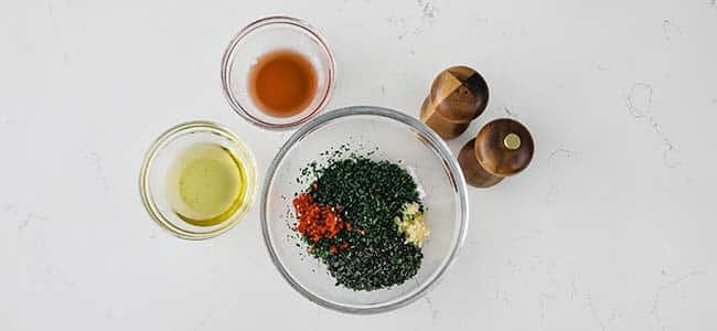 bowl of chopped herbs with oil and vinegar