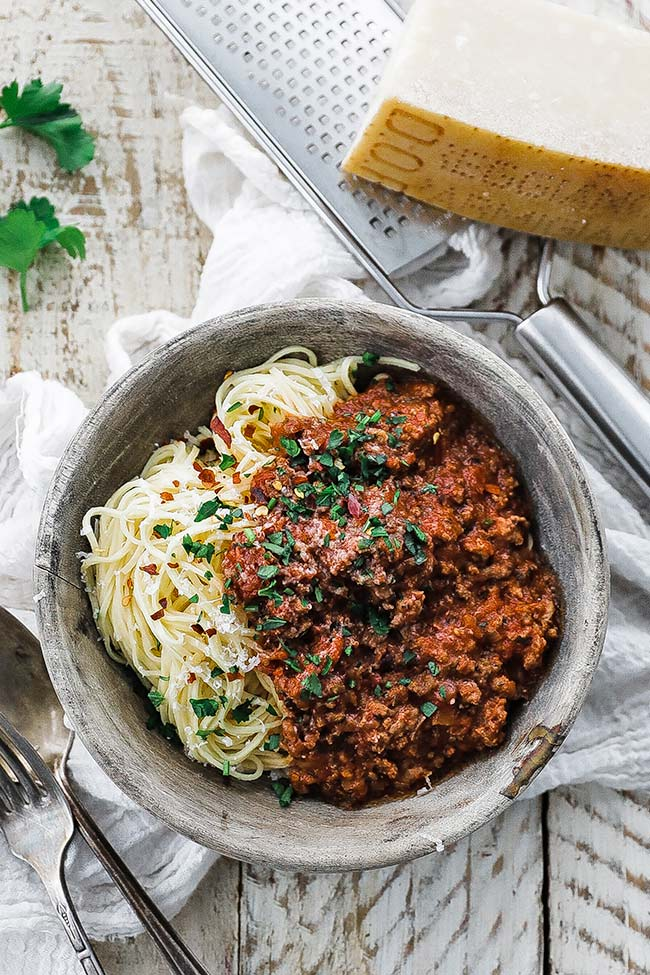 a bowl of fresh spaghetti and sauce with cheese and parsley