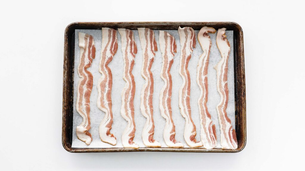 raw bacon on a sheet tray lined with parchment paper