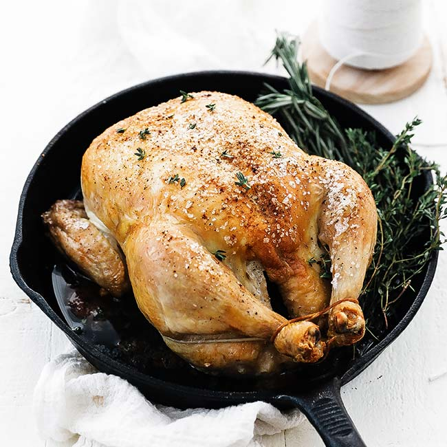 whole roast chicken with herbs in a cast iron pan