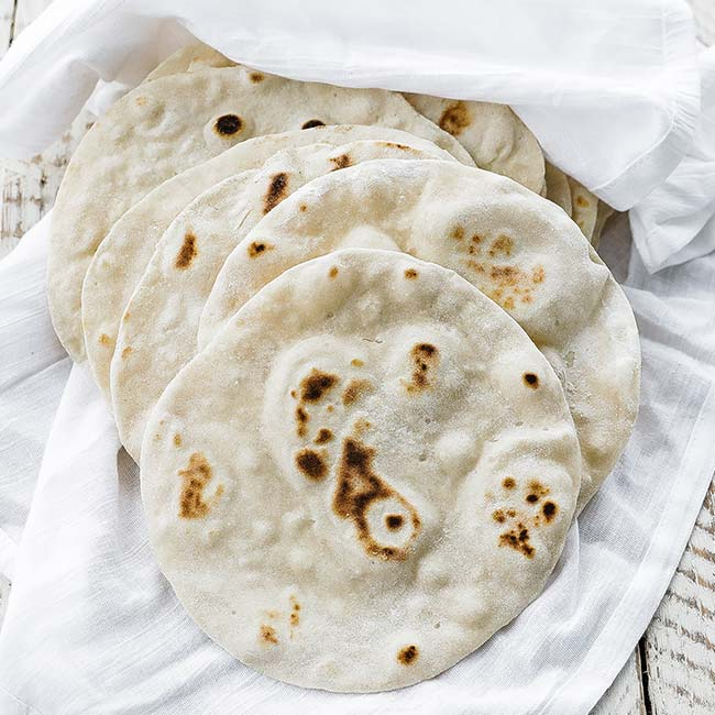 cooked flour tortillas in a cloth
