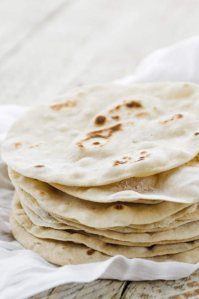 flour tortillas in a stack on cloth