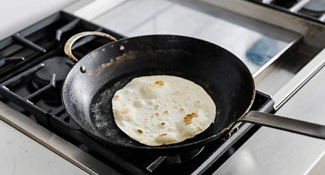 cooking a flour tortilla in a large pan