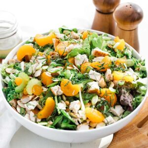 Mandarin orange salad in a bowl with herbs and chicken