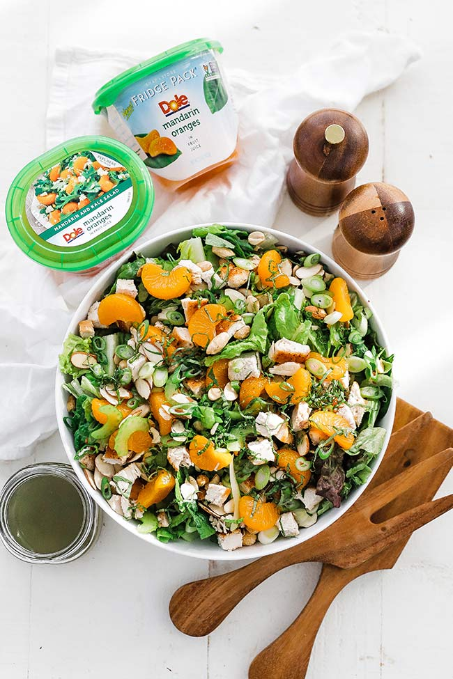 bowl of greens with oranges and nuts