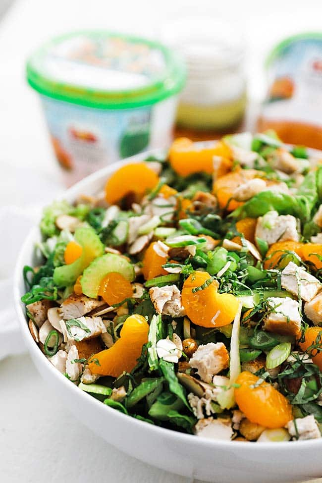 greens salad with almonds and chicken in a bowl