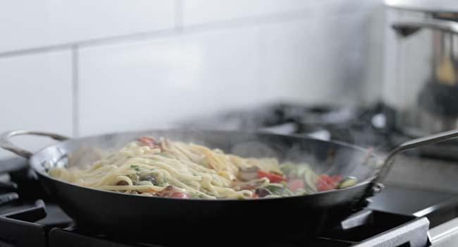 tossing the cooked vegetables with pasta