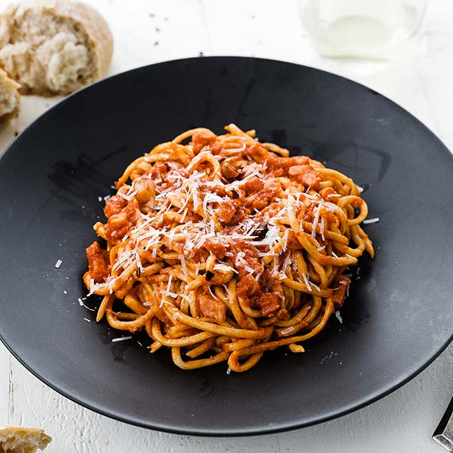 bowl of bucatini pasta with tomato sauce and cheese