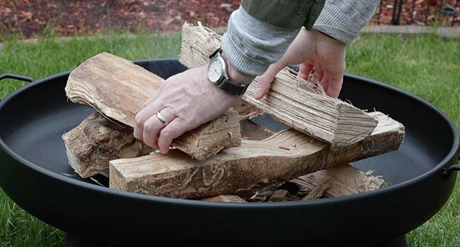 adding two logs to a log stack in a fire pit
