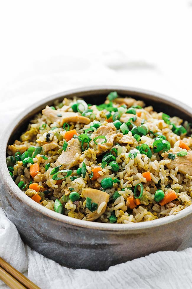 chicken fried rice recipe in a bowl with green onions
