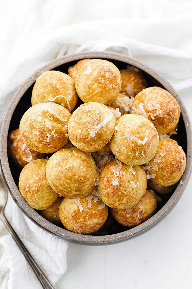 bowl of baked gougeres with shredded cheese