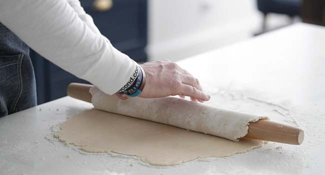 rolling pie dough around a rolling pin