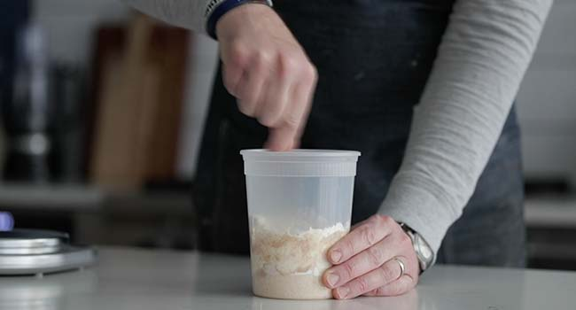 mixing together a sourdough starter in a plastic container