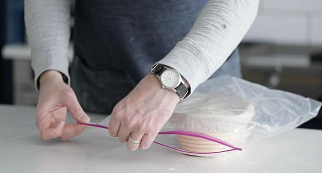 adding dough in a bannetton to a large plastic zip bag