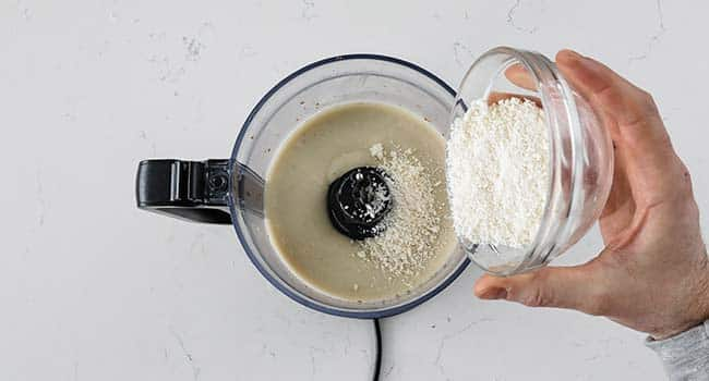 pouring in grated parmesan cheese to caesar salad dressing in a food processor